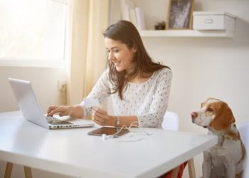 Young Caucasian businesswoman using credit card for on line payment. her dog next to her crm and remarketing